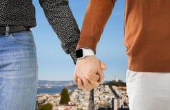 关闭有smartwatch的男性快乐夫妇手 库存图片
