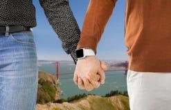 关闭有smartwatch的男性快乐夫妇手 免版税库存图片