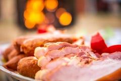 关闭未加工的烟肉、香肠和辣椒粉在五颜六色的盘子,准备为烤肉 发光的格栅在背景中 库存图片