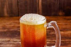 关闭杯与泡沫的啤酒在一张木桌上在一间黑暗的客栈 免版税库存图片