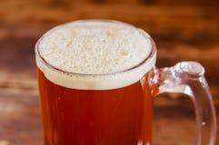 关闭杯与泡沫的啤酒在一张木桌上在一间黑暗的客栈 库存照片