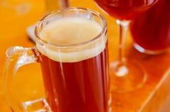 关闭杯与泡沫的啤酒在一张木桌上 图库摄影