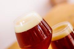 关闭杯与泡沫的黑啤酒在一张木桌上 免版税库存照片