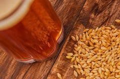 关闭杯啤酒用在基地的麦子在一张木桌上 免版税库存照片
