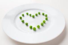 关闭板材用在心脏形状的豌豆 免版税库存照片