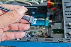 关闭架线计算机零件的技术员的手 图库摄影