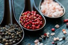 关闭桃红色喜马拉雅盐和胡椒在匙子 库存图片