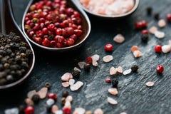 关闭桃红色喜马拉雅盐和胡椒在匙子 免版税库存图片