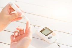 关闭检查血糖水平的妇女手由葡萄糖我 免版税库存照片