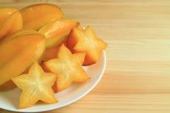 关闭橙黄色成熟整个果子和切的阳桃在白色板材在木桌上服务,与自由空间文本的 免版税库存照片