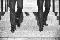 关闭步行沿着向下台阶的两商人的腿在现代城市 免版税库存照片