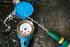 关闭水表蓝色颜色 并且有流动的水的一个水管 库存照片