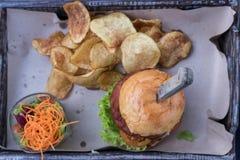 关闭汉堡用火腿、乳酪、莴苣和菜,装饰与在一个木板的土豆片油煎的和调味汁 免版税库存图片