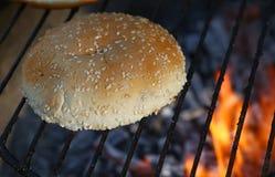 关闭汉堡的芝麻小圆面包在bbq火格栅 图库摄影
