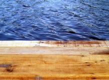 关闭江边大阳台和美好的小波纹老木板条大海表面上 免版税库存照片