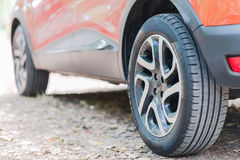 关闭汽车轮胎 一辆停放的汽车的后面看法在用秋叶盖的路的 免版税库存照片