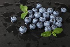 关闭洗涤了在黑人委员会的新鲜的蓝莓 库存图片
