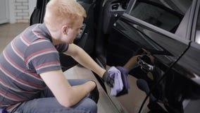 关闭洗车的一名男性工作者的射击小心地擦亮与一块干毛巾的汽车防御者 影视素材