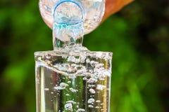 关闭流动从饮用水瓶的水入在被弄脏的绿色庭院背景的玻璃 库存照片