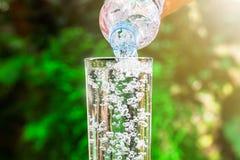 关闭流动从饮用水瓶的水入在被弄脏的绿色自然背景的玻璃 库存照片