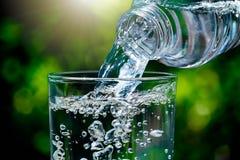 关闭流动从饮用水瓶的水入在被弄脏的绿色自然bokeh背景的玻璃与软的阳光 图库摄影