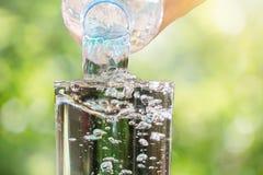 关闭流动从饮用水瓶的水入在被弄脏的绿色bokeh背景的玻璃 免版税库存照片