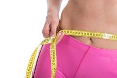 关闭测量有测量的女性手黄色磁带腰部 白色背景的适合和健康妇女 免版税库存照片