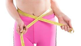 关闭测量有测量的女性手黄色磁带腰部 白色背景的适合和健康妇女 库存图片