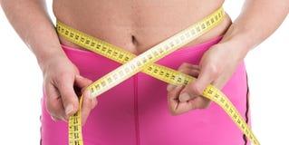 关闭测量有测量的女性手黄色磁带腰部 白色背景的适合和健康妇女 库存照片