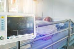 关闭测量的心脏和血压显示器的数字式重要标志与年长耐心睡眠在床上 库存照片