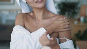 关闭浴巾的妇女应用奶油于肩膀,慢动作 股票录像
