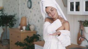 关闭浴巾的美女应用奶油于脖子,肩膀,慢动作 股票视频