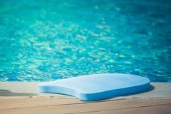 关闭游泳泡沫在游泳池边缘的板谎言有大海背景 免版税库存照片