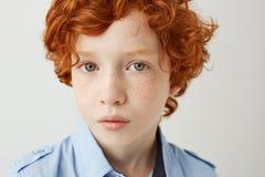 关闭滑稽的小孩画象有橙色头发和雀斑的 看在与轻松和镇静面孔的照相机的男孩 库存照片
