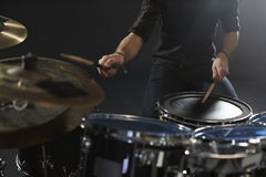 关闭演奏鼓成套工具的鼓手在演播室 库存照片