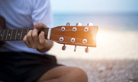 关闭演奏经典吉他开会的英俊的人 免版税库存图片