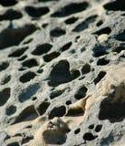 关闭灰色在海滩的被腐蚀的岩石,用沙子盖 库存图片