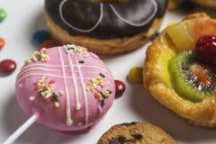 关闭点心用糖果、巧克力和草莓油炸圈饼和水果蛋糕 库存照片