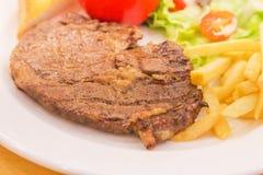 关闭烤烤肉牛排用炸薯条和菜土豆 图库摄影
