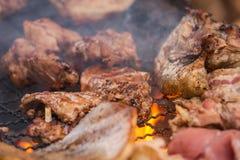关闭烤肉在木炭格栅的猪肉烧烤与明亮的火焰 免版税库存图片