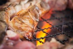 关闭烤肉在木炭格栅的猪肉烧烤与明亮的火焰 图库摄影