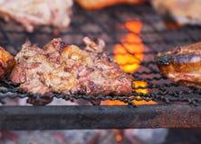 关闭烤肉在木炭格栅的猪肉烧烤与明亮的火焰 库存图片