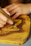 关闭烧与烙画笔的手木头射击 图库摄影