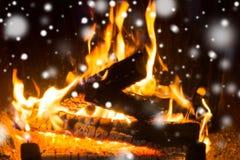 关闭烧在壁炉和雪的木柴 库存图片