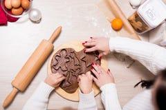 关闭烹调圣诞节曲奇饼的女孩和她的母亲 库存照片