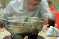 关闭烹调有烟的热的罐在被弄脏的背景 选择聚焦和浅景深 库存图片