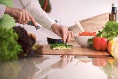 关闭烹调菜沙拉的人的手在玻璃桌上的厨房里与反射 健康膳食,和 免版税库存照片