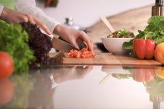 关闭烹调菜沙拉的人的手在玻璃桌上的厨房里与反射 健康膳食,和 免版税库存图片