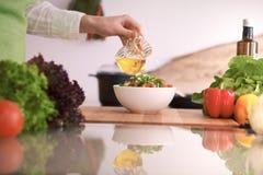关闭烹调菜沙拉的人的手在玻璃桌上的厨房里与反射 健康膳食,和 库存照片