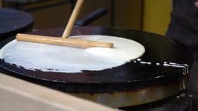 关闭烹调薄煎饼的厨师 厨师倒液体面团入一个热的煎锅并且传播与专辑的面团 股票视频